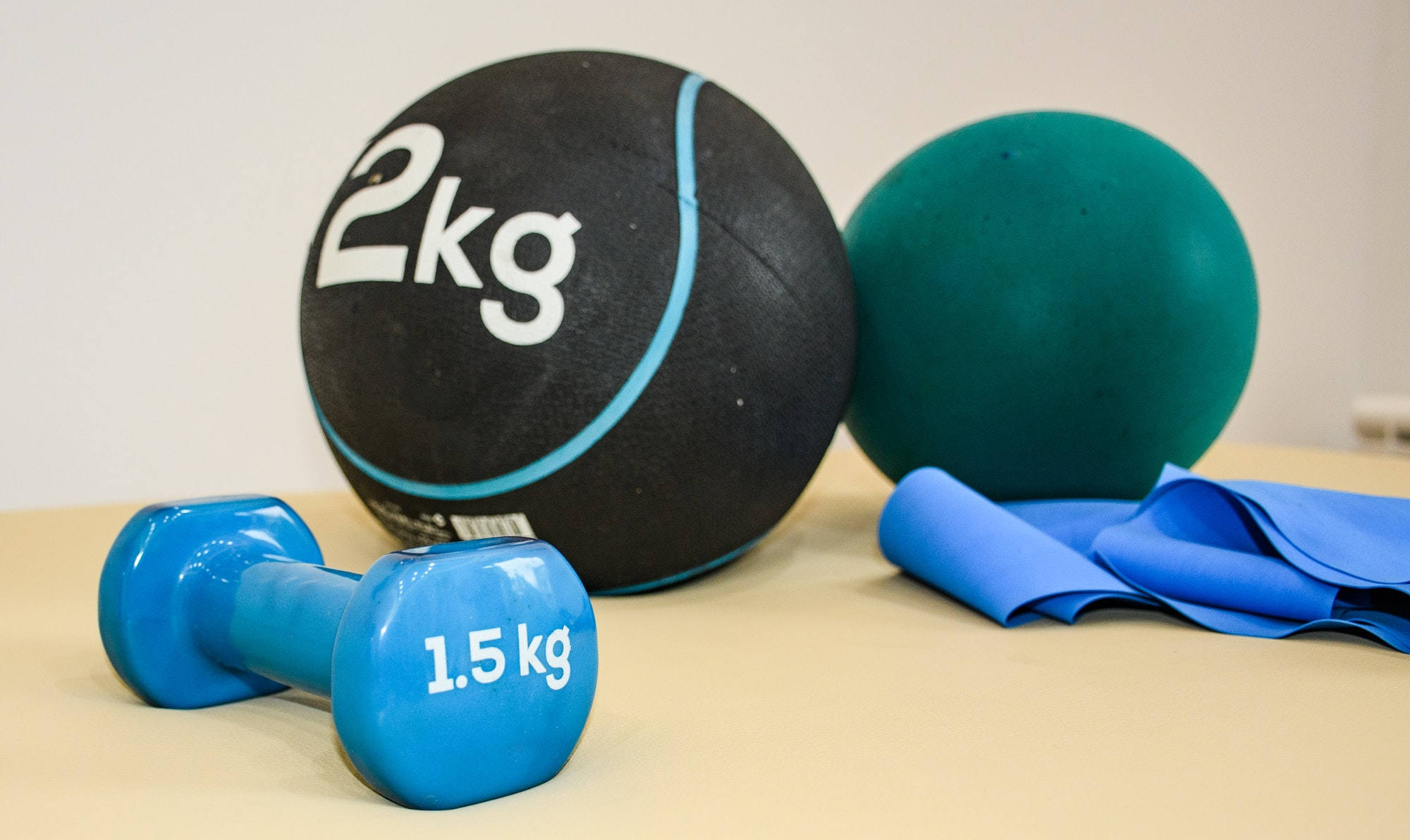 Close-up of workout gear, fitness equipment. Restistance band, med ball, dumbbell.